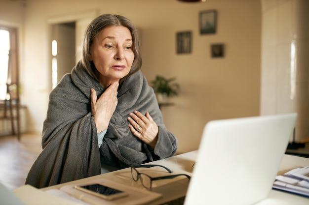 屋内でポーズをとる表情豊かな年配の女性