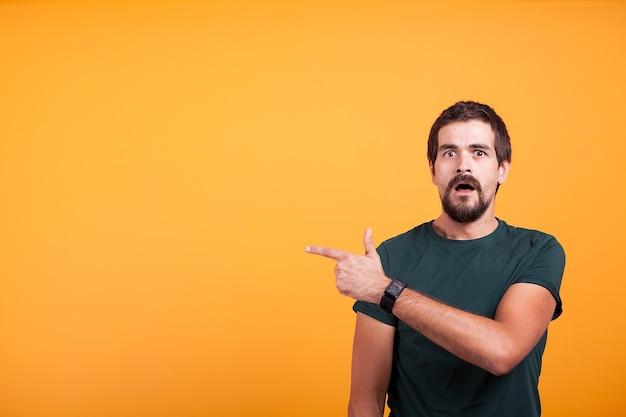 オレンジ色の背景に口を開けて右を指している表情豊かなショックを受けた男。あなたの広告やプロモーションに利用できるコピースペースを指して驚いた男
