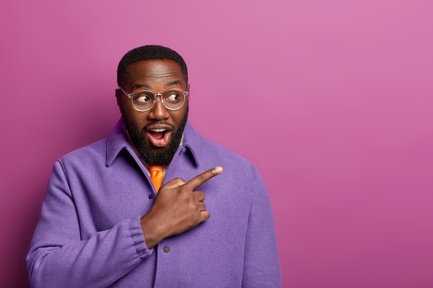 Expressive surprised black man points right with index finger and says wow, sees shocking things, wears purple jacket