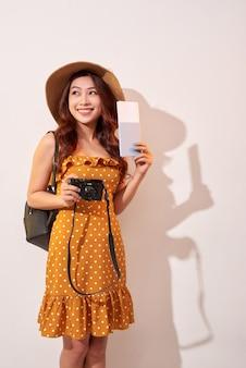 夏のカジュアルな服装、パスポートを保持している帽子、ベージュの壁で隔離のチケットで表現力豊かな観光客の女性。週末の休暇を旅行するために海外に旅行する女性。飛行機の旅のコンセプト