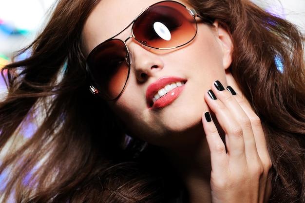 モダンな茶色のファッションサングラスと美しいブルネットの女性の表現力豊かなビュー
