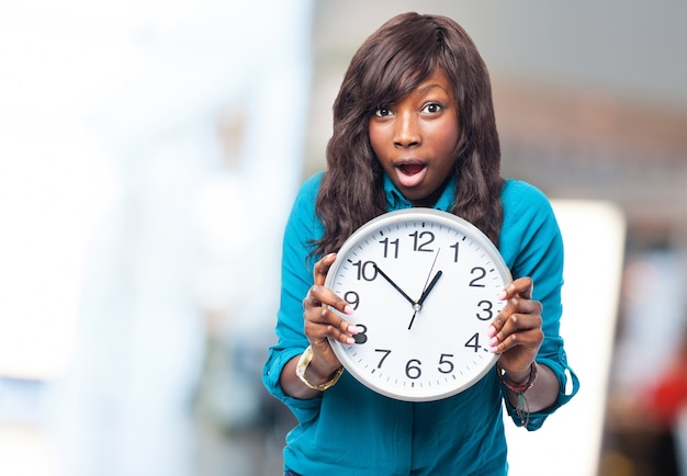 Expressive woman holding a clock