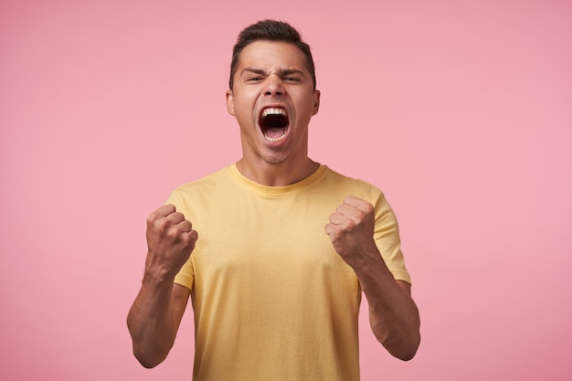 Expressive young handsome brown haired male raising excitedly his fists and shouting emotionally with wide mouth opened, isolated over pink background