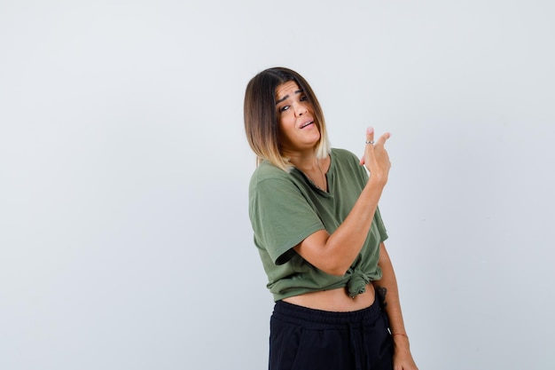 スタジオでポーズをとる表情豊かな若い女性