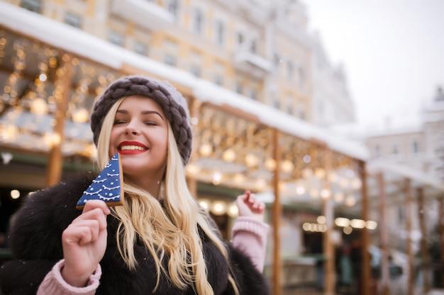 毛皮のコートとニット帽を身に着けて、通りで明るい装飾に対しておいしいクリスマスのジンジャーブレッドを保持している表現力豊かな若い女性