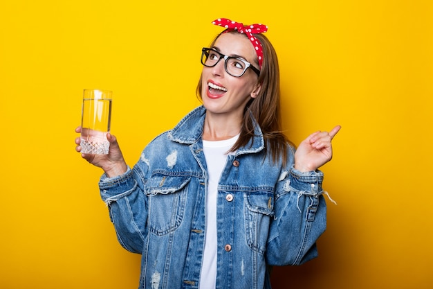 ジーンズ、メガネ、きれいな水のガラスを保持しているヘッドバンドで表現力豊かな若い女性