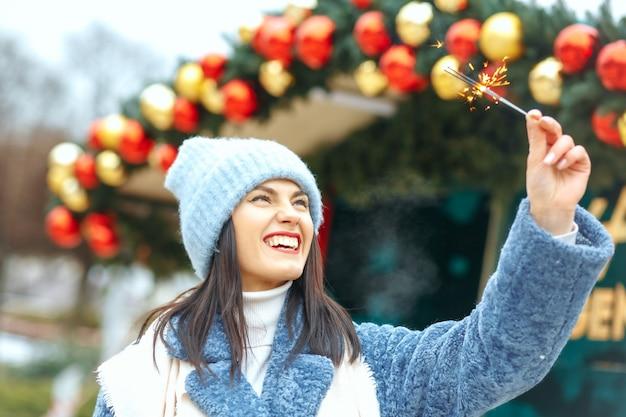 表情豊かな若い女性は、ベンガルライトで休日を楽しんで青いコートを着ています