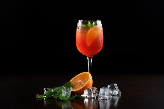 차가운 음료수, 오렌지 슬라이스, 신선한 그린 민트 잎 및 투명한 얼음 조각이있는 키가 큰 크리스탈 칵테일 잔으로 절묘한 구성