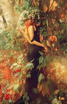 Exquisite girl in a dress with an open back standing in the woods with hop on head outdoors