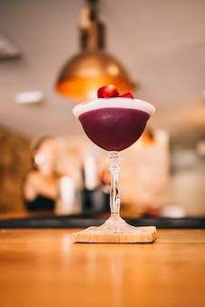 Изысканный бордово-красный коктейль в специальном бокале на деревянной барной стойке на фоне барной стойки