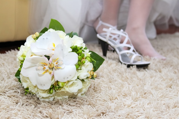 Exquisite wedding bouquet of white flowers: freesias, phalaenopsis orchids and roses. bride's shoes in the background