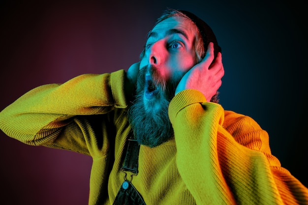 Exremely shocked, astonished. caucasian man's portrait on gradient studio background in neon light. beautiful male model with hipster style. concept of human emotions, facial expression, sales, ad.