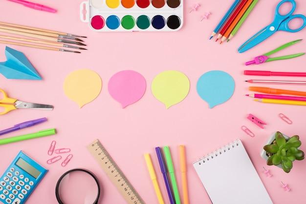 Выражение мыслей и идей в школе и концепции работы. концепция коммуникации. вверху над головой вид фото красочных канцелярских бумажных облаков и суккулентов, изолированных на пастельно-розовом фоне