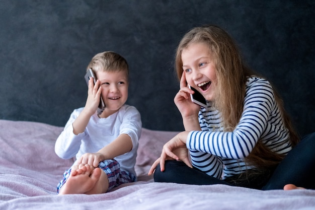 Exsited kids caucasian boy and girl speak on the mobile phones at home.