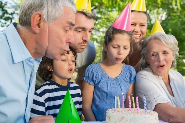 誕生日のケーキを吹くパーティー・ハットの家族の拡大