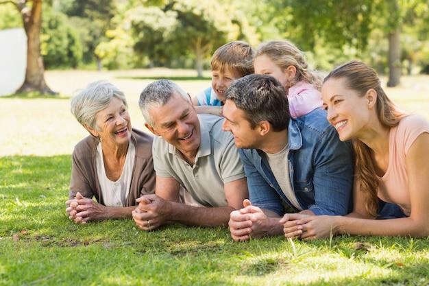 Extended family lying on grass in park