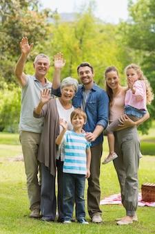 Расширенная семья размахивая руками в парке