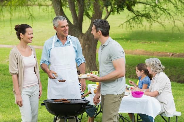 Расширенная семья с барбекю в парке