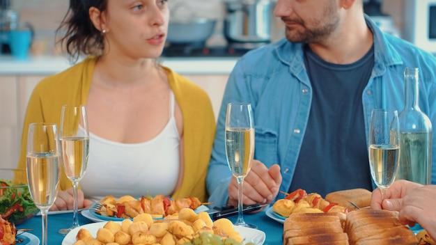 キッチンのテーブルに座って夕食時に乾杯する幸せな家族を延長しました。お祝いの居心地の良いパーティー中に見られる白ワインのグラス。