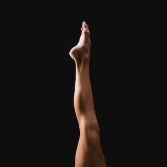 Extended leg against black background