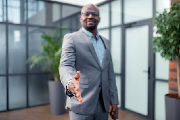 Протягивая руку. крупный план темнокожего бизнесмена, протягивающего руку деловому партнеру