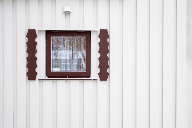 Exterior close wooden window with curtain on timber wall house