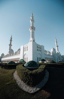 Exterior corner view of huge white mosque with white arch dome