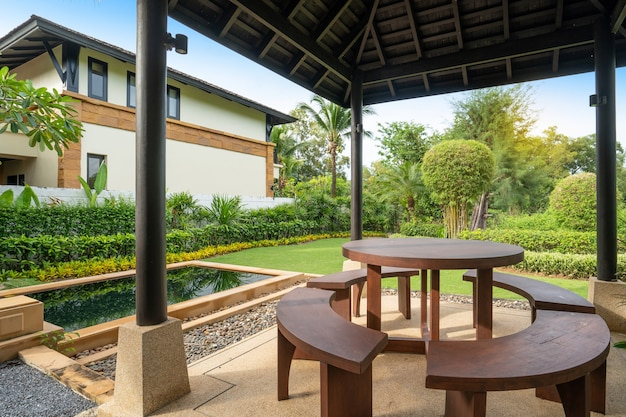 Exterior design of house, home feature garden landscape with outdoor table and chair in pavilion and swimming pool