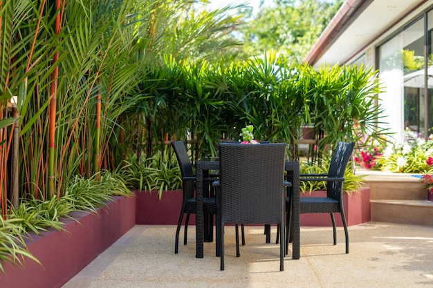 Exterior design of house, home and villa feature outdoor dining table and dining chair in the garden surrounded by a green plants
