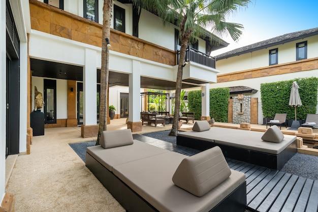 Внешний вид дома, дома и виллы с шезлонгами, пальмами, зонтиком и душем на открытом воздухе на террасе у бассейна.
