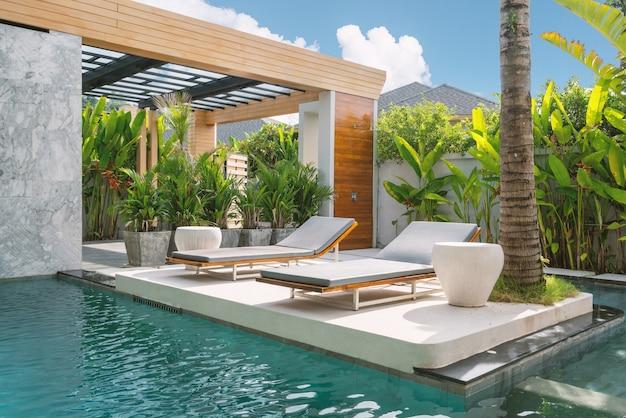 家、家、別荘のエクステリアデザインはサンラウンジャーを備え、青い空と緑の植物があります