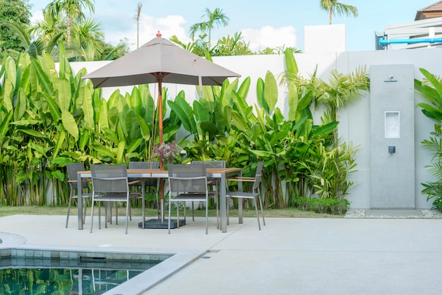 Exterior design outdoor table by    with umbrella at swimming pool of the house or home building