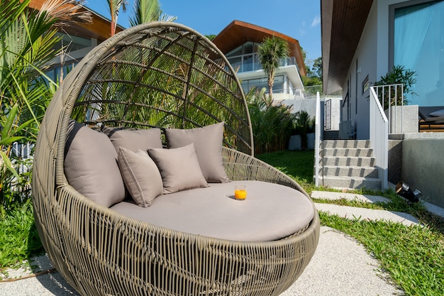 Exterior design of villa, house and home feature round shape sun bed and cushion by swimming pool
