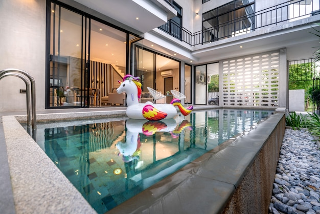 Exterior home with swimming pool and floating unicorn in the house