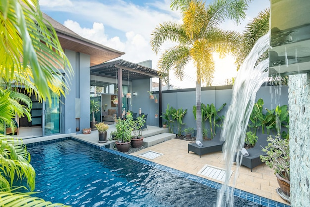 Exterior  and interior design showing tropical pool villa with green garden, with sun bed and blue sky