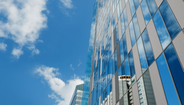Exterior of modern glass office building in urban city on sunny day