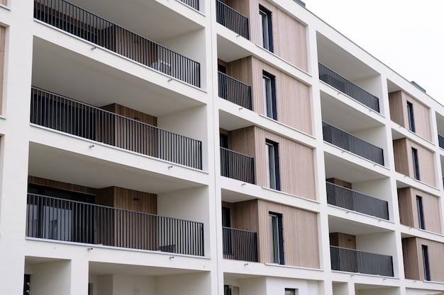 Exterior of new modern white apartment building with balcony in contemporary residential district.