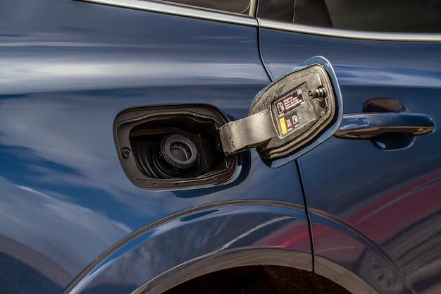 Внешний вид автомобиля с открытой дверцей заливной горловины. открыта крышка топливного бака автомобиля для заправки бензина или дизельного топлива в бак. дверца топливного бака открыта, а крышка топливного бака закрыта.