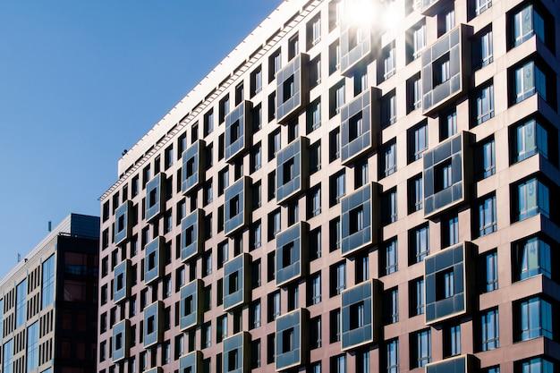 市内中心部の近代建築の外観。建設の抽象的な背景。窓付きのファサードの詳細。