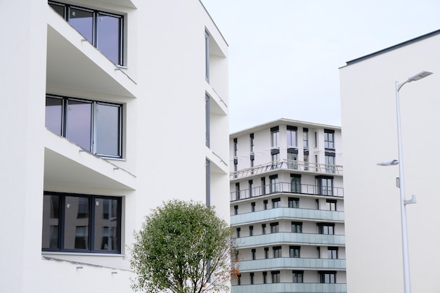Exteriors of modern white apartment buildings with balcony in contemporary residential district.