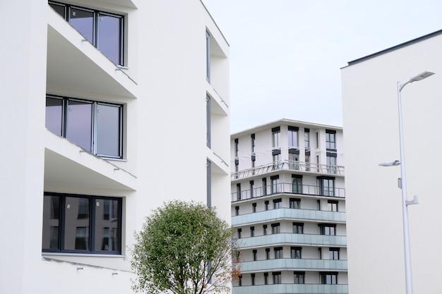 現代的な住宅街にあるバルコニー付きのモダンな白いアパートの外観。