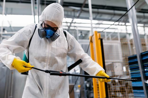 噴霧器で農薬を噴霧する産業プラントの害虫駆除業者。