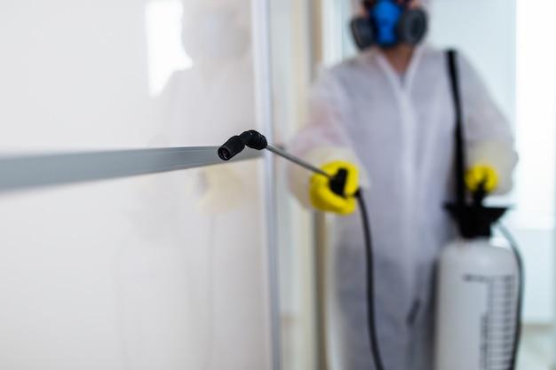 噴霧器で農薬を噴霧する作業着の害虫駆除業者。