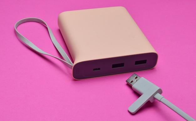 ピンク色の背景にusbケーブルをクローズアップしてスマートフォンやガジェットを充電するための外部バッテリー。パワー・バンク。現代のテクノロジー。