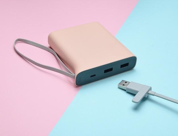 ピンクブルーのパステル調の背景にusbケーブルのクローズアップでスマートフォンやガジェットを充電するための外部バッテリー。パワー・バンク。現代のテクノロジー。