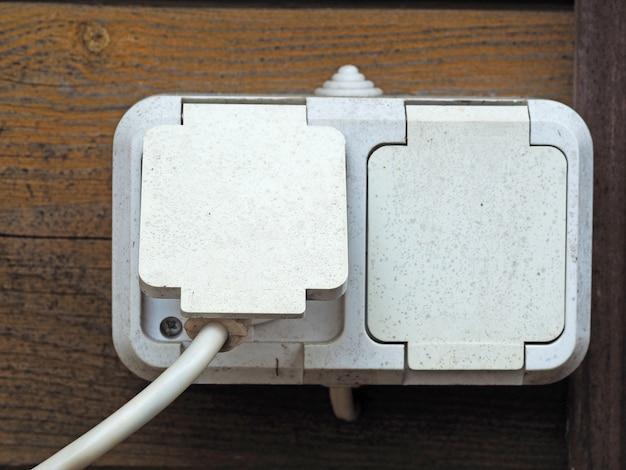 집의 나무 벽에 있는 외부 전기 콘센트. 습기로부터 보호되는 플라스틱 소켓