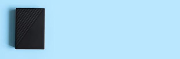 Внешний жесткий диск черного цвета на синем фоне. место для текста. знамя