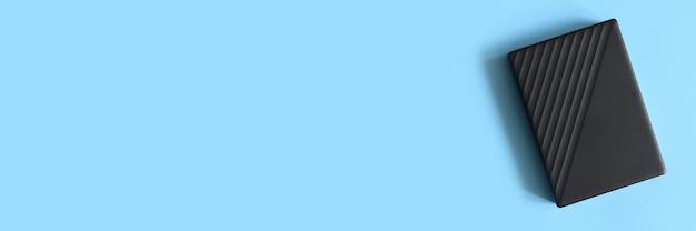 青の背景に外付けハードドライブの黒い色。テキスト用のスペース。バナー