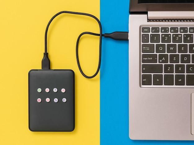 青と黄色の背景でラップトップに接続されている外付けハードドライブ。上からの眺め。バックアップストレージの概念。フラットレイ。