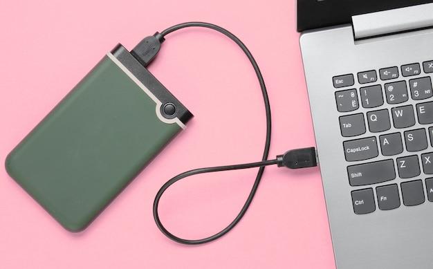 ピンクのラップトップに接続された外付けハードドライブ